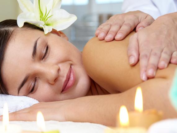 Młoda kobieta uśmiecha się podczas masażu