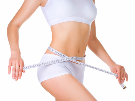 Szczupła kobieta mierzy się centymetrem w talii.