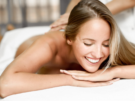 Młoda blondynka uśmiecha się podczas masażu w SPA